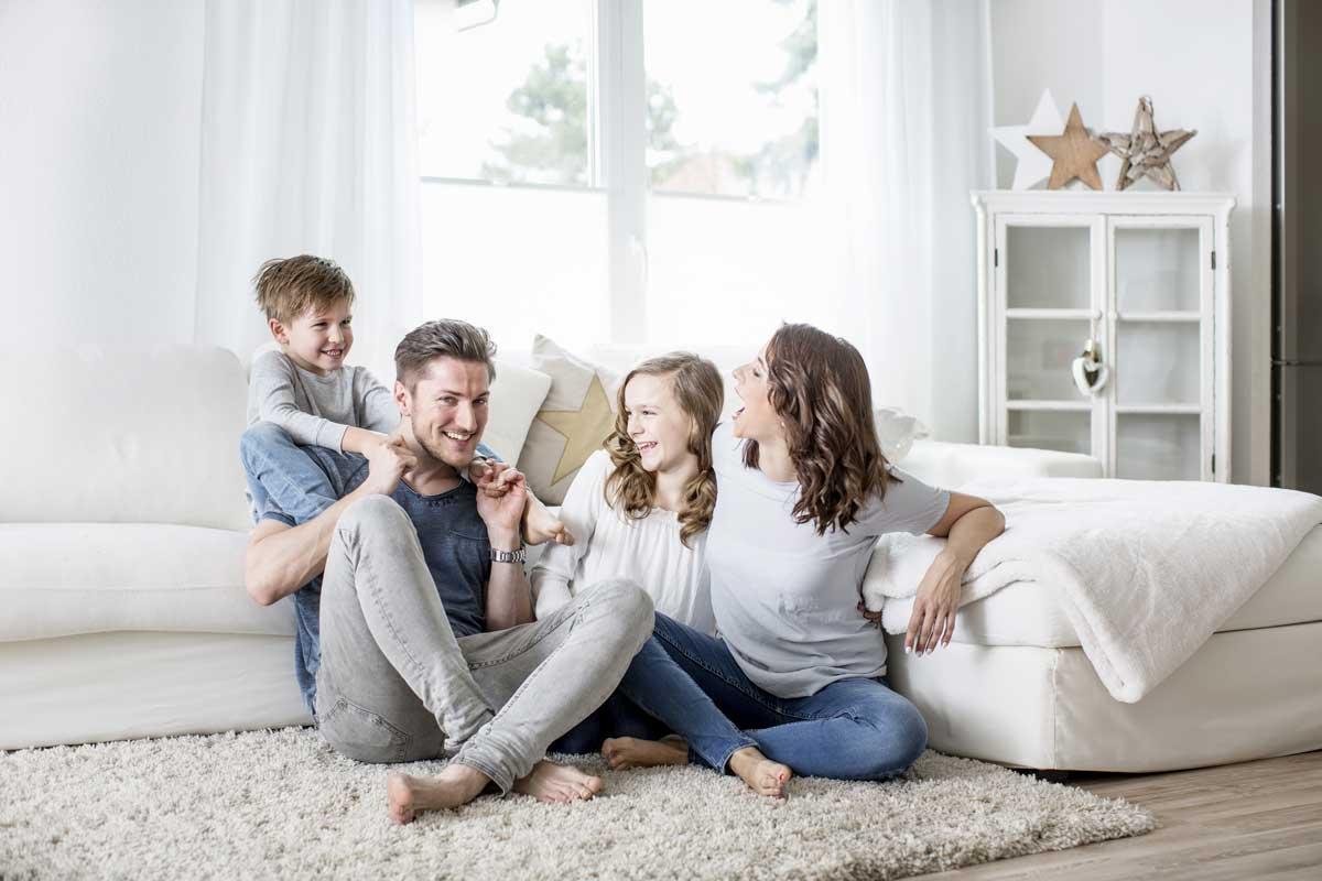 Imagen de familia en el suelo de casa, cómodos y con temperatura agradable
